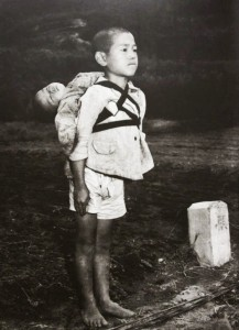 10-JAPanese boy standing at attention after having brought his dead younger brother to a cremation pyre, 1945
