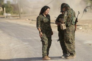 (x)Female fighters of the Kurdish People's Protection Units (YPG) carry their weapons as they talk along a road in Qamishli countryside September 19, 2014.