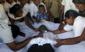 In this Feb. 5, 2014, photo, family members weep around the body of Seneviratnalage Jayatillake, a Sri Lankan farmer who suffered from a chronic kidney disease of unknown etiology, during his funeral in Padaviya, Sri Lanka. The cause of his disease, which affects anywhere from an estimated 70,000 to 400,000 people in Sri Lanka's rice basket, remains an enigma without a name. It mirrors an equally confounding condition plaguing thousands of farmworkers in parts of India, Egypt and Central America, where chronic dehydration is one suspected cause. (AP Photo/Eranga Jayawardena)