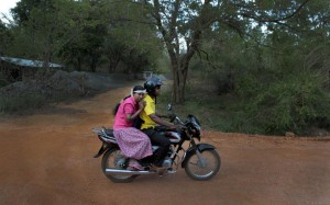 In this July 24, 2014, photo, V.G. Karunawathie, left, a patient suffering from a chronic kidney disease of unknown etiology, leans on her son as she rides home from a hospital after a dialysis session in Konketiyawa village in Padaviya, Sri Lanka. She received treatment on her second visit the same day to the tiny nearby hospital as there were not enough dialysis units to go around. (AP Photo/Eranga Jayawardena)